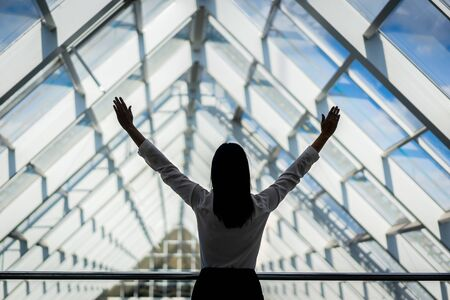 Successful Woman. Happy Young Woman Raising Hands Up To The Sky. In big business centre 版權商用圖片