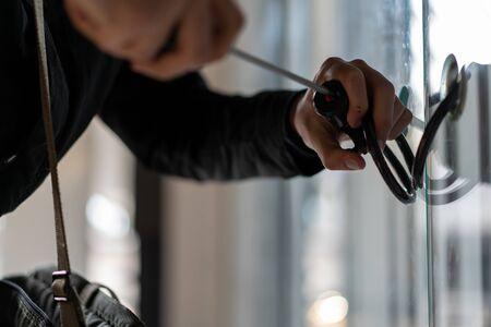 Man using screwdriver to open glass door . Burglar breaking in. Burglary. 版權商用圖片