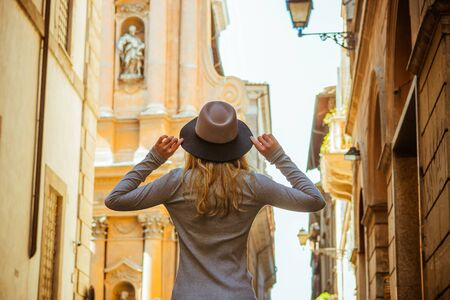 Back view of woman wearing grey sweater. Nice hat, hands up. Beautiful architecture.