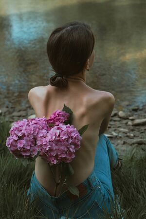Portrait of a beautiful lady from the back, topless. Attractive brunette with some flowers in her jeans