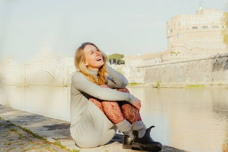 Rear View of a Smiley Young Woman Facing at the River while Sitting on a Long Concrete Bench and Hugging her Legs 版權商用圖片