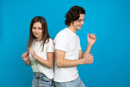 Happy couple in white t-shirts dancing isolated on blue background. 版權商用圖片