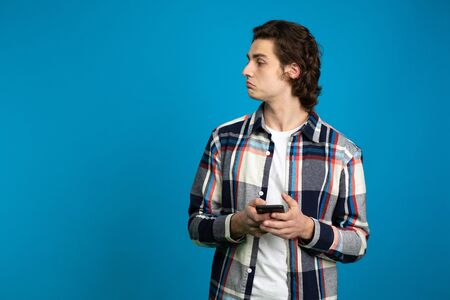 Brunette young man holding smartphone isolated on blue background.