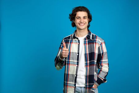 Smiling young man showing thumb up isolated on blue background.
