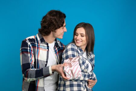 Smiling man presenting gift to girlfriend isolated on blue background.