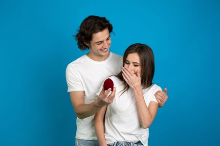 Young man proposing to surprised girlfriend isolated on blue background. 版權商用圖片
