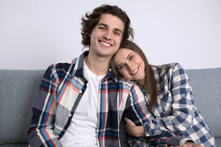 Happy young couple on sofa looking at camera in living room.