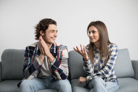 Young couple talking and laughing on sofa in living room.