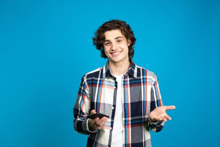 Front view of smiling young man with smartphone isolated on blue background.