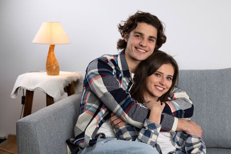 Smiling young man embracing girlfriend on couch.