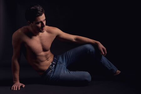 Stylish guy without a shirt on the floor looking to the side and thought