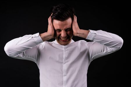 isolated young guy in a white shirt covers his ears.