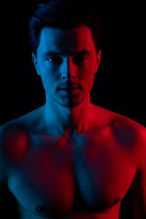 Man in studio with red and blue colors. Look at camera and smile 版權商用圖片