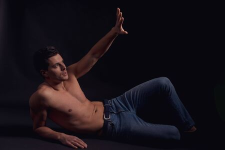 young attractive guy with a naked body covered by hand from the light