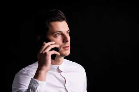 Isolated young man with phone in hands look somewhere and thinking