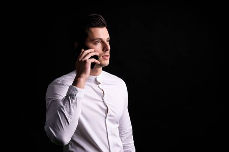 Isolated young man with phone in hands look somewehere and thinking