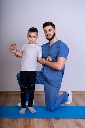 A young doctor in blue uniform stands on the knee on a blue pad and holding with both hands the boy's shoulders Stock Photo