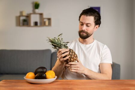 A young man sits at a table and talks about the usefulness of fruits, he picks them up and shows pineapple, avocado, orange. Healthy food Reklamní fotografie
