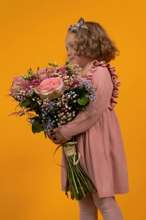 Cute little girl in a pink dress, curly hair with a bow holding a large bouquet of pink flowers in her hands, full-length profile, vertical postcard
