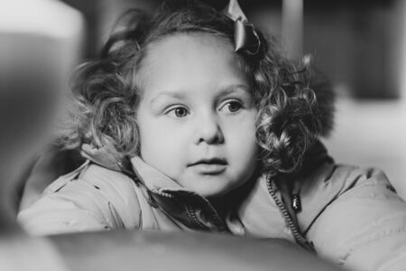 Portrait of a little curly girl, she smiles cute, black and white photo, postcard Stock fotó