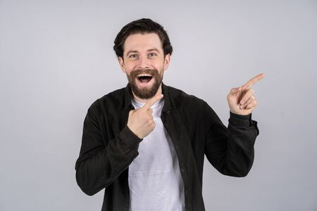 A man with a beard looking directly at the camera and pointing finger in the direction Stock fotó