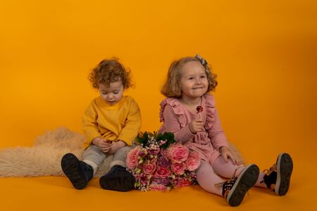 Cute little boy and girl are sitting on a fluffy rug with a bouquet of flowers, yellow background, concept of holiday, joy and happiness in the house