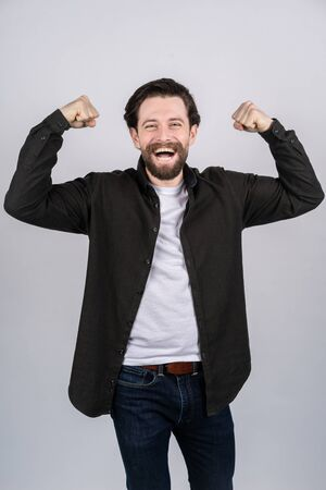 Young man with beard showing a gesture of power, he cheerfully laughs