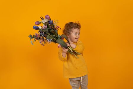 Cute little boy with curly hair holds in his hands a bouquet with multi-colored tulips, yellow background, the concept of a holiday and gifts Stock fotó