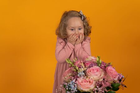 Cute little girl in a pink dress, curly hair with a bow looks at a bouquet of beautiful flowers and closes her mouth with hands in surprise, a concept of a holiday and gifts