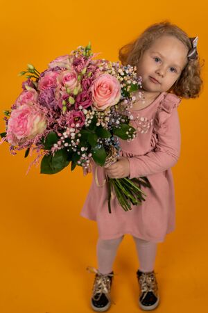 Cute little girl in a pink dress, curly hair with a bow holding a large bouquet of pink flowers in her hands, full-length, vertical postcard Stock fotó