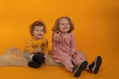 Cute little boy and girl sitting on a fluffy rug with lollipops, yellow background, concept of holiday, joy and happiness in the house Stock fotó
