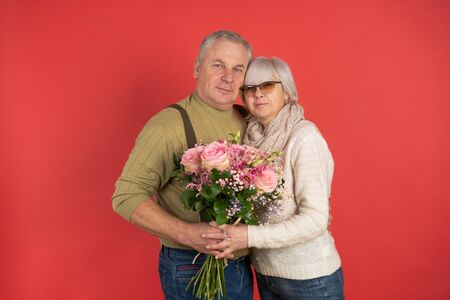 An elderly man gives a beautiful bouquet of flowers to an elderly woman, wife, colleague, friend, red background, the concept of happy old age