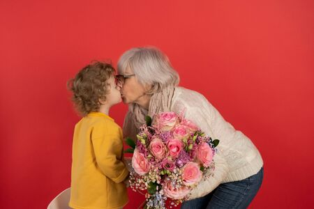 Cute little boy with curly hair gives his grandmother a bouquet of tulips, red background, holiday and gift concept.