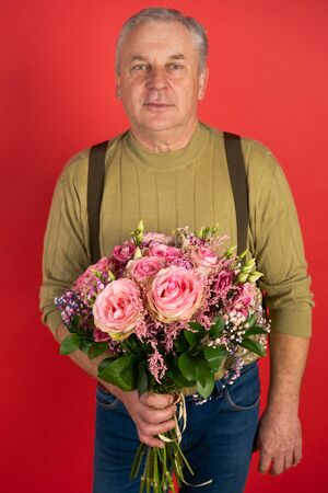 An elderly man with a large beautiful bouquet of flowers stands on a red background, the concept of a holiday and a happy old age