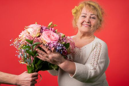 hands of a young woman giving a bouquet of tulips to an elderly woman.march 8, mother's day concept
