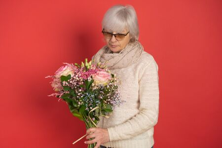 Happy senior woman with bouquet of flowers on color background Stock fotó