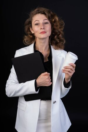 A young woman in a business suit with a document case in one hand and tea in another, curly hair, a distant look Stock fotó