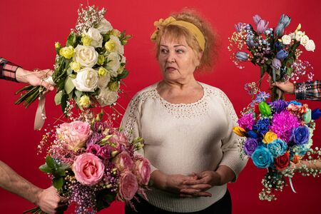An aged woman is surrounded by flowers, blue, yellow, white, pink - the woman is confused by abundance and colors, she seemed to think about the choice