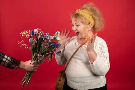 An aged woman receives a gift of a bouquet of beautiful flowers and is very emotionally responsive, she is happy and surprised at such a pleasant surprise Stock fotó