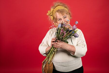 An aged woman holding a bouquet of beautiful flowers in her hands, she pressed it to her chest as if hugging, the concept of a welcome gift for a holiday, love and pleasure