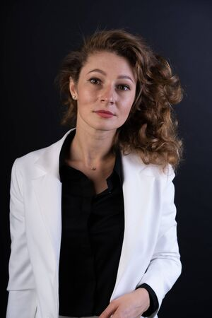 A young girl with curly hair in a white business suit and black shirt, looking confidently straight Stock fotó