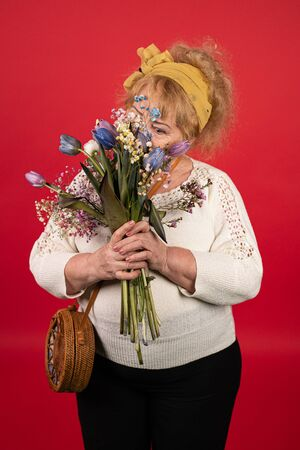 An aged woman holds a bouquet of beautiful blue tulips in her hands, she inhales their aroma to enjoy a gift, the concept of a desired gift for a holiday, love and pleasure.