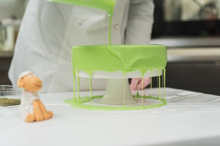 Pastry cook prepares a cake of green, watering it with icing Stock fotó