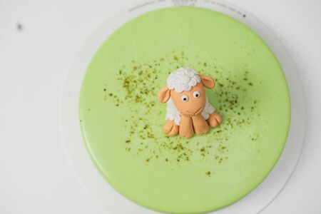 A beautiful cake is green, it sits a sugar lamb as the grass, spring design Stock fotó