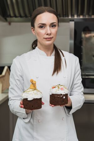 Woman pastry chef holds Easter cakes, she in a white tunic on the professional kitchen Stock fotó