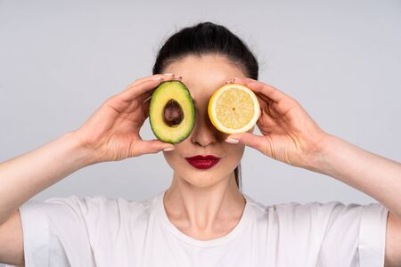 Girl in white shirt holds the halves of the avocado and orange right next to the eye, the concept of beauty and health