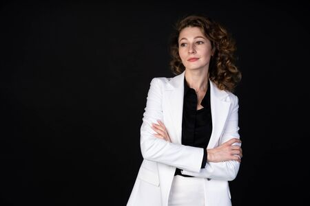Stylish business woman in white suit standing with arms folded, she is calm and confident, black background