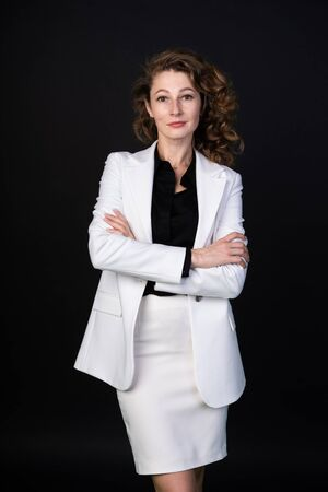 Stylish business woman in white suit standing with arms folded, she is calm and confident