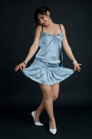 Pretty brunette girl with collected hair, in light blue dress looking at camera smiling and bowing, on black background, long shot