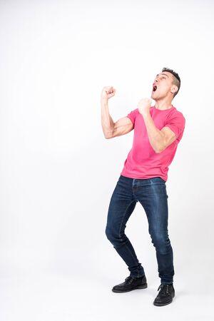 Euphoric man celebrating something. White background. Full body Stock Photo